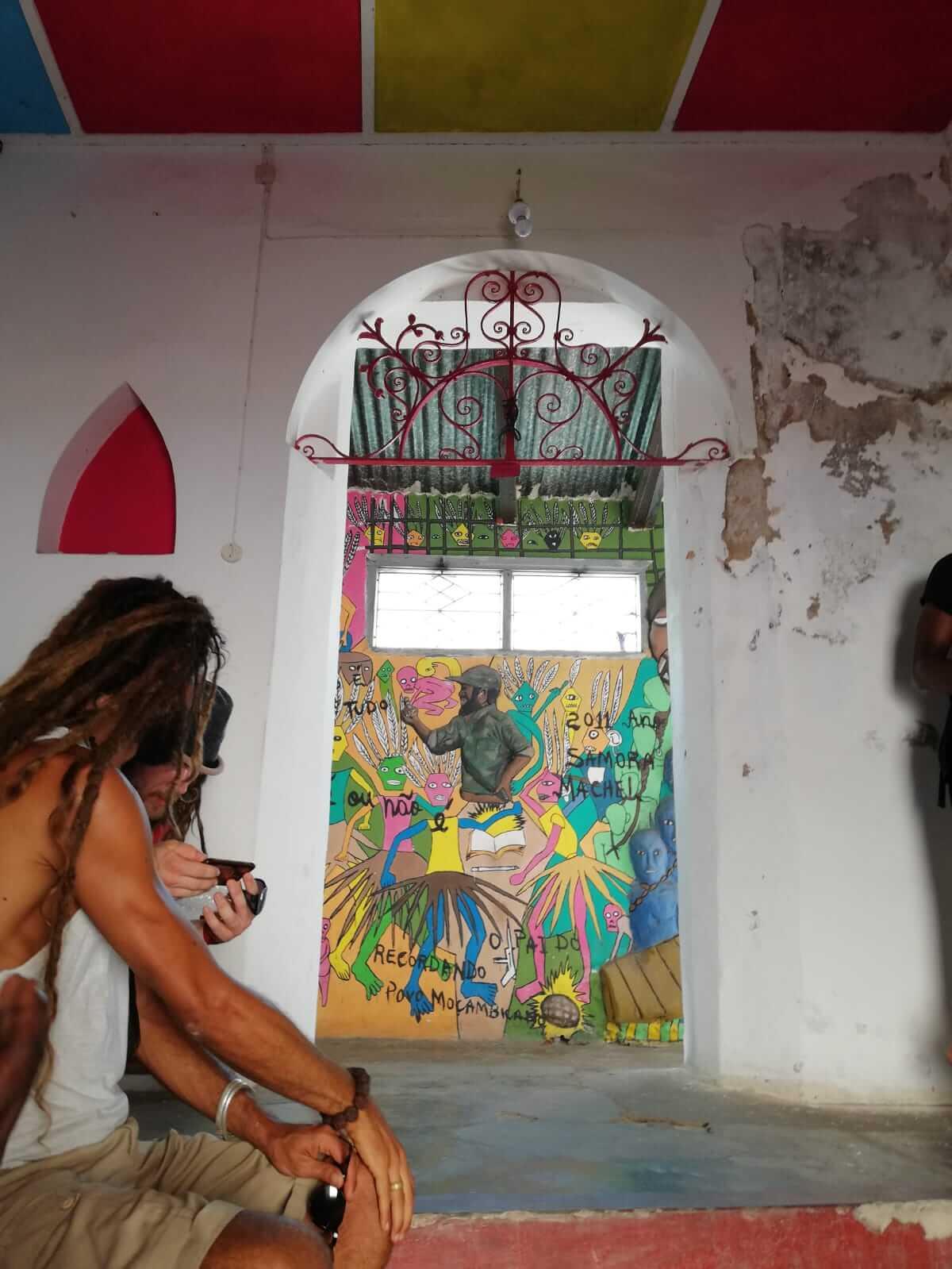 turistas sentados a apreciar grafitis