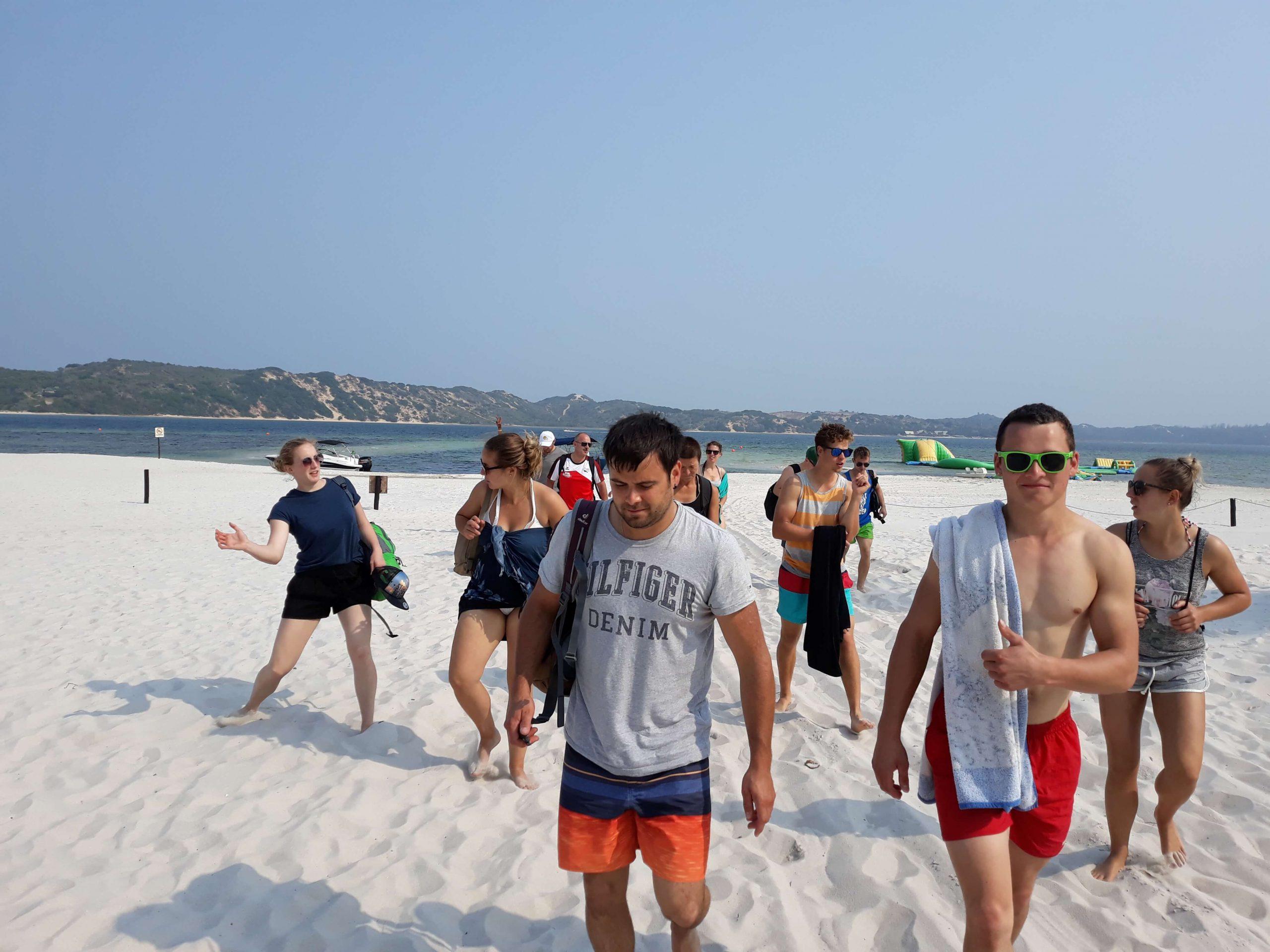 grupo de viajantes a sair da praia
